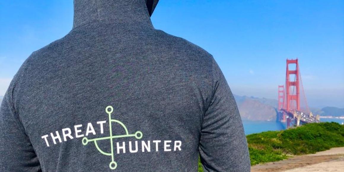 """man wearing """"threat hunter"""" sweatshirt looking at Golden Gate Bridge"""
